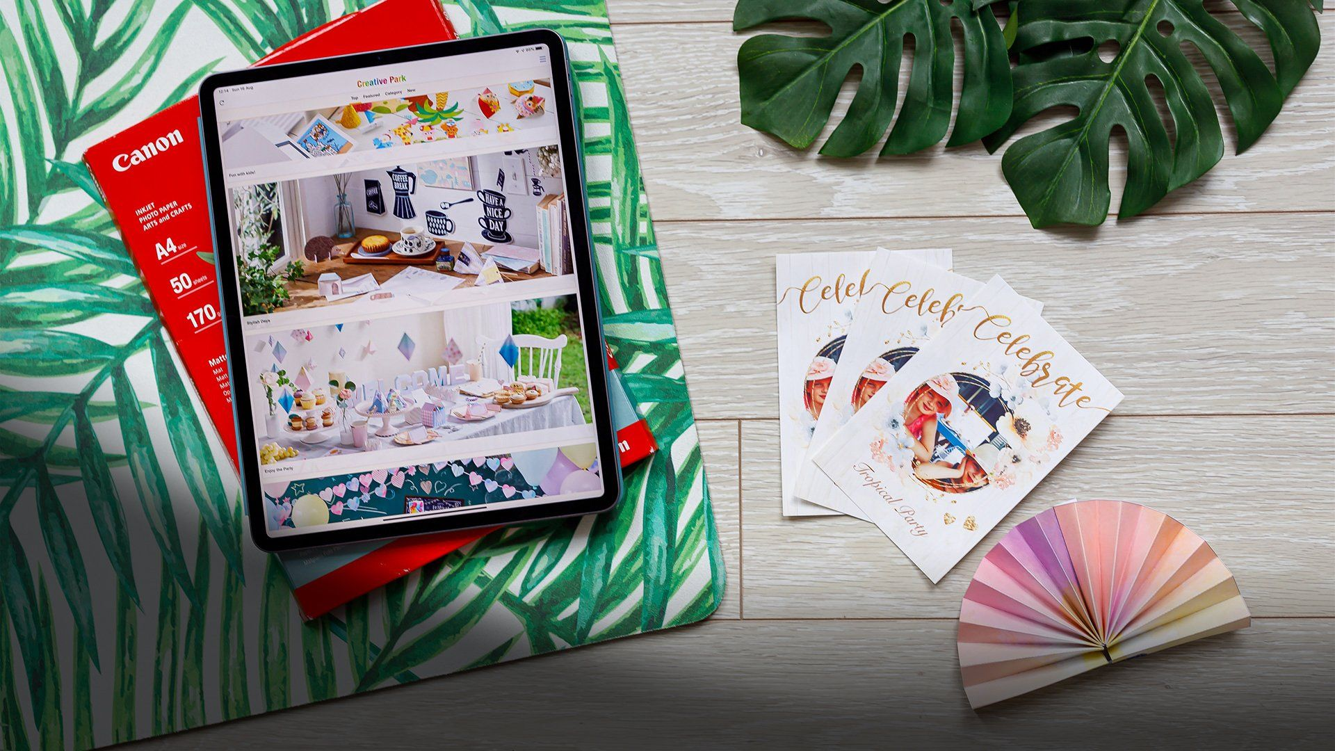 A tablet showing the Creative Park app next to personalised cards and a party garland.